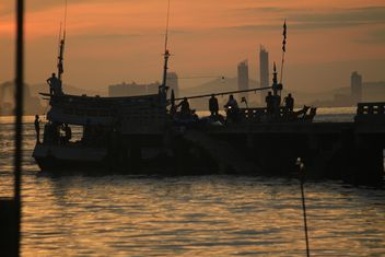 Silhouettes of fishermen in boat at sunset - Free image #348661