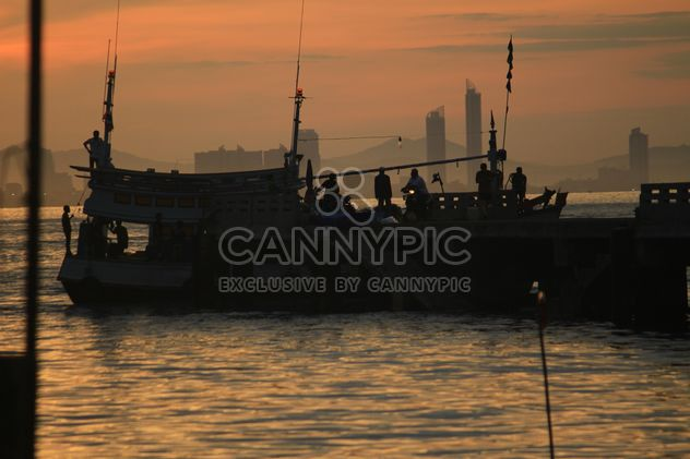 Silhouettes of fishermen in boat at sunset - бесплатный image #348661