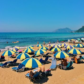 People under umbrellas on beach - бесплатный image #363661