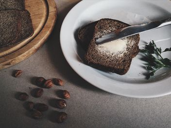 Breakfast. bread and butter on a plate and chopped bread on a wooden board - бесплатный image #373531