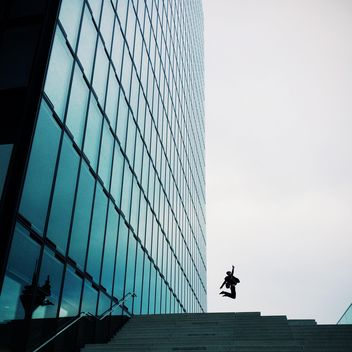 Man jumping by Modern building exterior with glass and metallic facade - image #439121 gratis