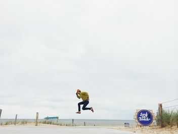 man jump at beach near sea - image #439211 gratis