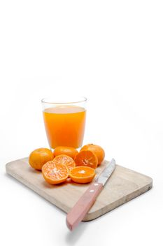 Oranges on the desk with knife and glass of juice on white background - image #452521 gratis
