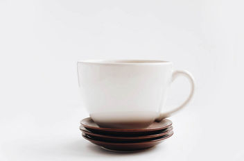 Big white cup and dessert plates on white background. - image #452721 gratis