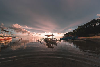 Sunset peaking behind a pumpboat in Sipalay - image #456731 gratis