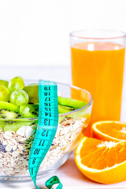 A proper diet for good health and a beautiful body - cereals with fresh fruit and a glas of orange juice with a measuring tape - бесплатный image #456791