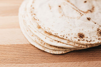 Stack of pita bread on wooden board - Free image #456981