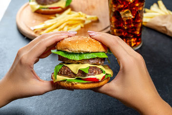 A woman holding a large hamburger on the background of fast food - бесплатный image #464061