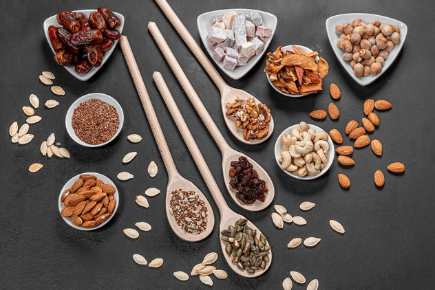 Top view dried fruits, nuts and seeds on a black background. Healthy food concept (Flip 2019) - Kostenloses image #464341
