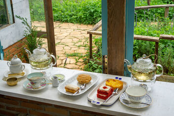 Glass Tea Pots, Tea Cups, Plates and other Ceramics on a Wooden Windowsill facing a Garden - image gratuit #475811
